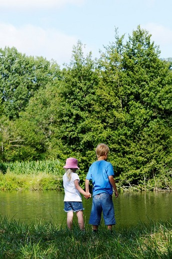 Stock Photo: 1566-559659 Brother and sister standing next to a river