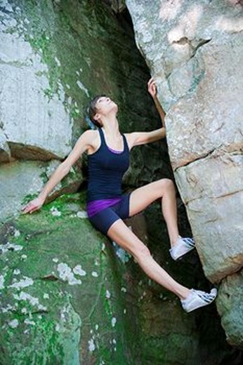 23 year old brunette woman dressed in exercise clothing perched in an opening in a rock wall : Stock Photo