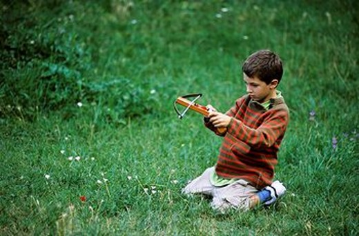 Stock Photo: 1566-560078 France provence boy sitting on the grass and playing with a crossbow