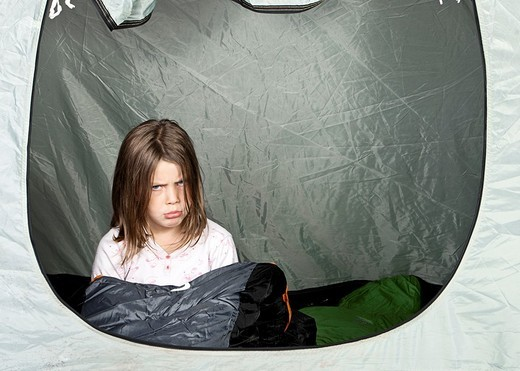 Shot of a Young Girl looking Unhappy in her Tent : Stock Photo