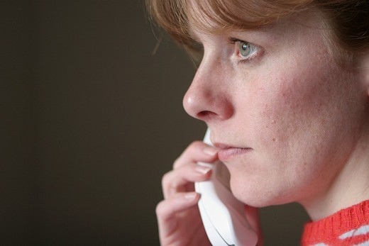 Stock Photo: 1566-560896 Thirty year old woman talking on the phone  Woman has red hair  Looking serious