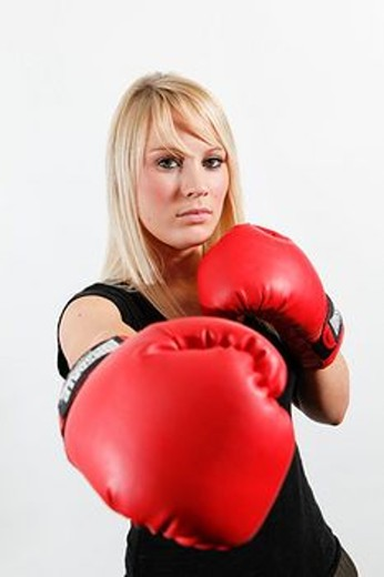 Stock Photo: 1566-560944 Boxing woman in red gloves and black top against white background  Blonde hair  Boxer