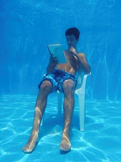 13 years old boy reading underwater : Stock Photo
