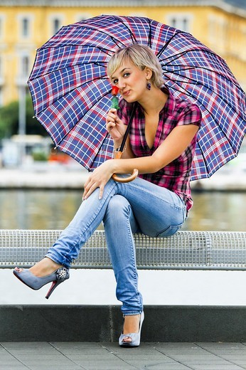 Sitting with a single rose in hand young woman is happy under an umbrella : Stock Photo