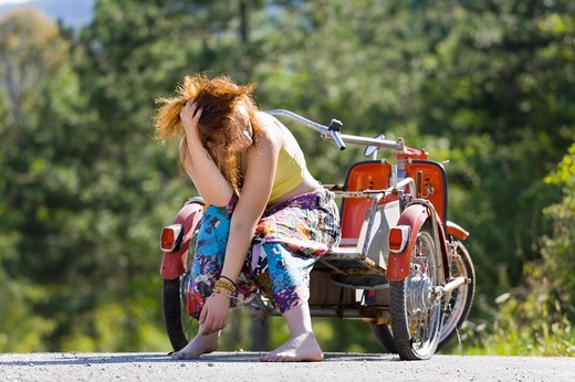 Stock Photo: 1566-561368 Young woman - troubles with a flat tire