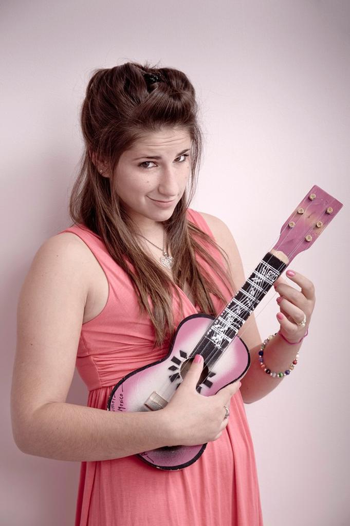 Stock Photo: 1566-561491 Teen girl playing a ukulele