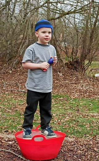 Stock Photo: 1566-561651 This Caucasian 5 year old boy is playing outside and standing on a red bucket that is frozen solid ice  He´s wearing a blue stocking cap, black sweat pants and holding a throwing toy  Background intentionally blurred to emphasize subject