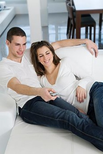Stock Photo: 1566-561812 Couple enjoying leisure at home watching TV