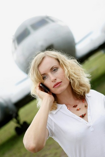 A business woman talking on a mobile phone next to a plane : Stock Photo