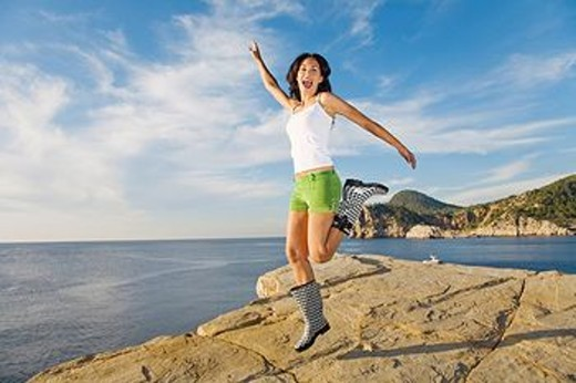 Stock Photo: 1566-564521 Brunette woman happy jumping in a cliff in Ibiza