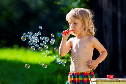boy with long blond hair blowing soap bubbles : Stock Photo