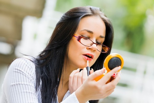 Stock Photo: 1566-566369 Applying lips make-up on the street young woman
