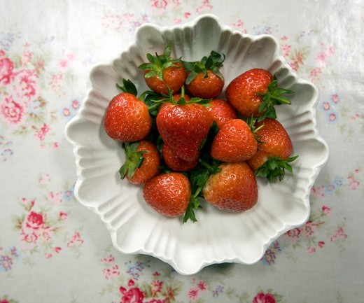 Stock Photo: 1566-571846 Looking down on white bowl fresh strawberries on floral tablecloth