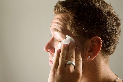 Young man wiping his face with a paper towel : Stock Photo