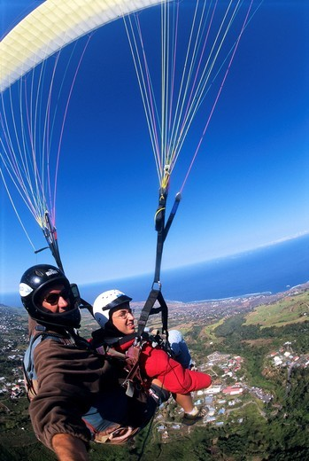 Two seater paraglider flying over Saint Leu countryside, Reunion Island France, Indian Ocean : Stock Photo