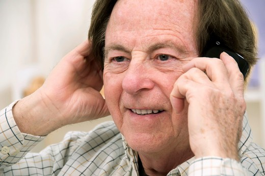 Stock Photo: 1566-574470 smiling senior man phoning, his telephone in one hand and his other hand on his ear