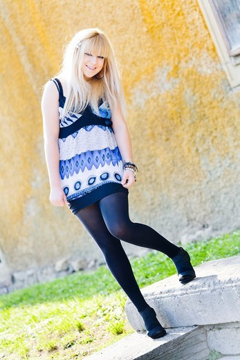 Blonde young woman is posing in a very short Blue minidress : Stock Photo