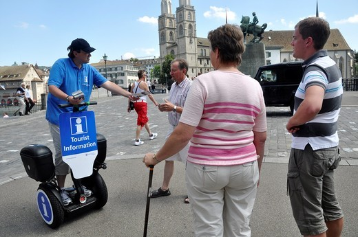 Zurich (Switzerland): a tourism board employee giving information to tourists in the city's center : Stock Photo