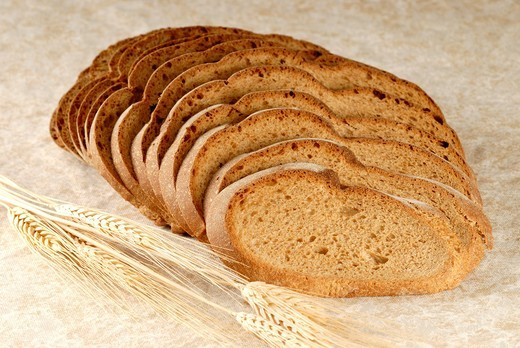 Stock Photo: 1566-576531 Loaf of fresh baked whole wheat bread cut into slices