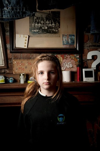 Interior, Sullen looking 12 year old girl, facing the camera, UK : Stock Photo
