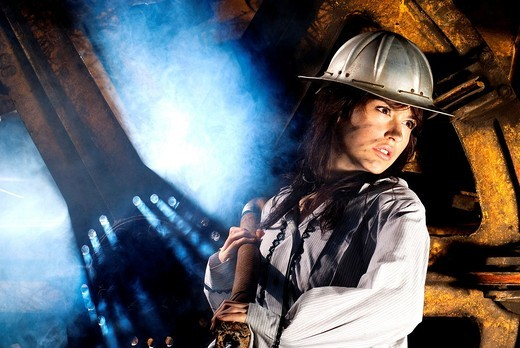 Stock Photo: 1566-582122 Representation of work in a mine made with a beautiful young woman with an aluminum hull pulling a steel cable with stained face and a dramatic lighting