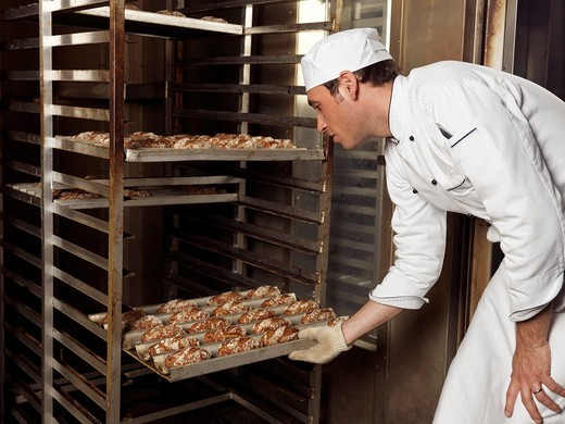 Stock Photo: 1566-582490 Portrait of a baker taking out a rack trolley with freshly baked buns out of a bakery oven