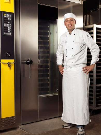Portrait of a smiling baker standing at a commercial bakery oven : Stock Photo