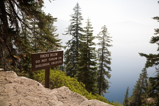 Sign posted along the Cleetwood Cove Trail  Sign reads ´Hikers Below - Do Not Throw or Dislodge Objects´  Morning mist obscures the rim and horizon line - Crater Lake National Park Oregon : Stock Photo