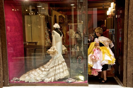 Typical sevillan wedding dress in a window shop on a dummy and shopkeeper with a heap of dresses on her arm SevillA Andalucia Spain : Stock Photo