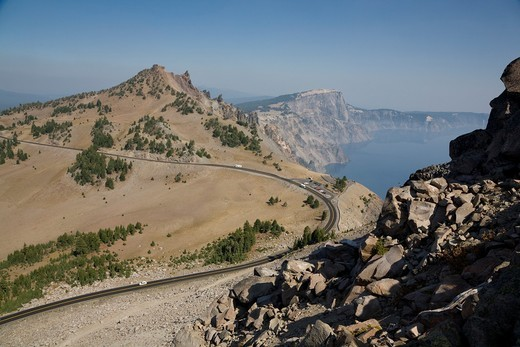 Route 7 rim drive - Crater Lake National Park Oregon  Rim Drive is a scenic highway in Crater Lake National Park in southern Oregon  It is a 33-mile loop that follows the caldera rim around Crater Lake  Because of the its unique engineering and the surrou : Stock Photo