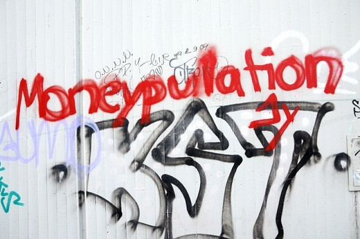 The lettering Moneypulation at a Cologne house wall : Stock Photo