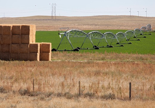Stock Photo: 1566-587880 Iliff, Colorado - Stacked hay next to irrigation equipment in the arid northeastern corner of Colorado