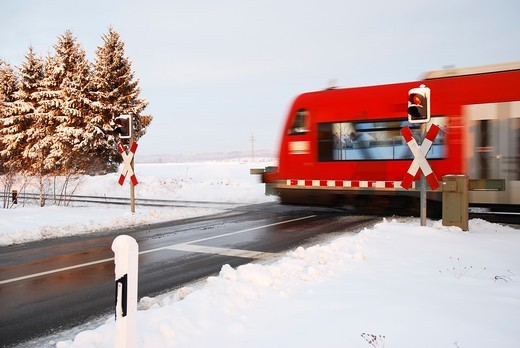 Stock Photo: 1566-589513 Regional train at a railroad crossing in winter