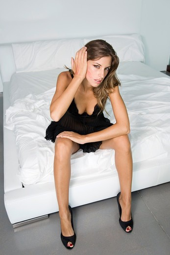 Stock Photo: 1566-591358 Woman sitting on bed, wearing high heels and lingerie