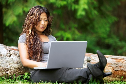 A beautiful young African American woman working on her laptop while sitting on a grass : Stock Photo