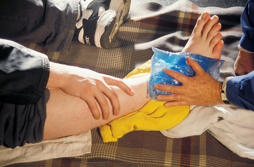 close up of ice pack being applied to a bruised leg : Stock Photo