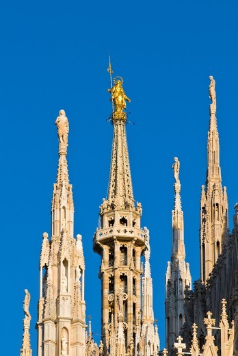 Italy, Milan, Madonnina statue on cathedral spire against blue sky : Stock Photo