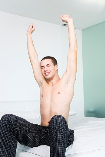 Man stretching sitting in bed : Stock Photo