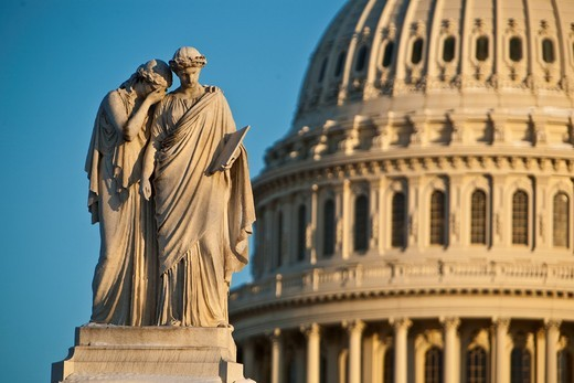 Two marble statutes of women in front of Capitol Dome : Stock Photo