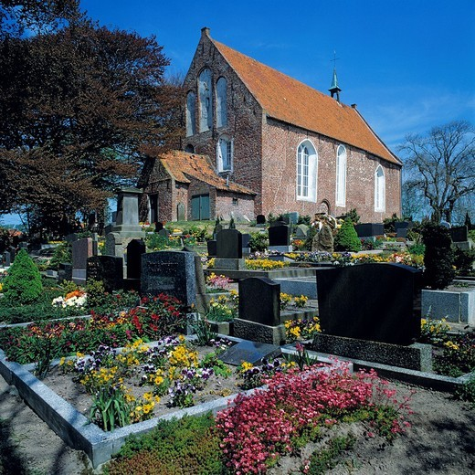 Germany, Dornum, North Sea, East Frisia, Eastern Frisia, Lower Saxony, Saint Bartholomaeus church, evangelic church, churchyard, graves, gravestones : Stock Photo