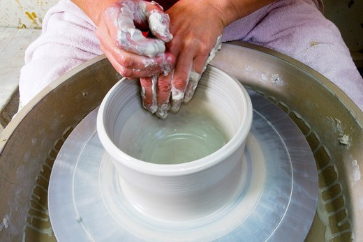 Stock Photo: 1566-600831 An European female potter in her workshop shapes clay on a potter´s wheel  Closeup of her hands