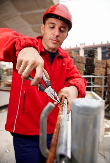 Worker using pliers in construction site, preparing concrete rods : Stock Photo