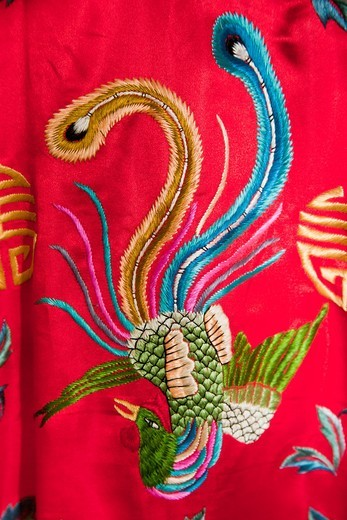 Stock Photo: 1566-604865 Colourful red Chinese embroidered silk garment depicting a phoenix bird, for sale, China