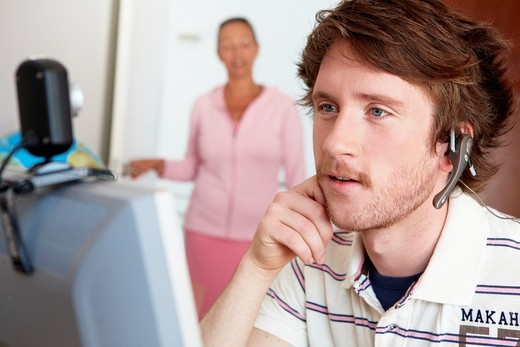 Mother calling son who is looking at computer in his room : Stock Photo