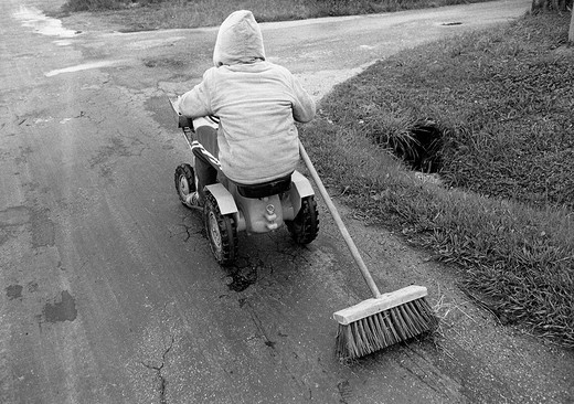 Eighties, black and white photo, people, children, little boy drives in a toy car along the street pulling a besom, street sweeper, aged 4 to 6 years : Stock Photo