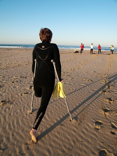 In Pismo Beach, California, Courtney Wilson, who lost one leg to cancer as an adolescent, moves towards the shore to participate in one of the regular Surf Clinics sponsored by AmpSurf, a Non-Profit Organization made up of amputees, veterans and friends & : Stock Photo