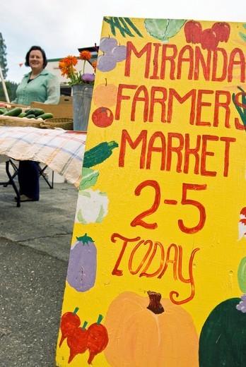 Woman selling produce at farmers market, Miranda California : Stock Photo