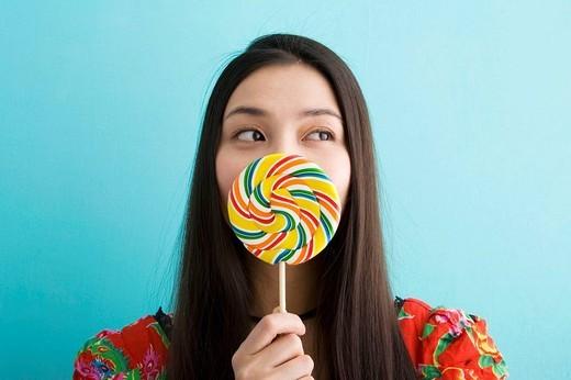 Woman eating lollipop : Stock Photo