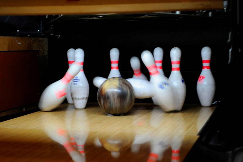 Stock Photo: 1566-616553 Black Bowling Ball Hitting White Bowling Pins