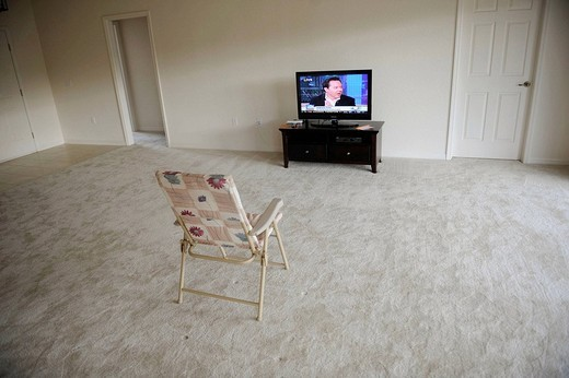 Stock Photo: 1566-616557 Flat Panel LCD TV Television sits alone in empty living room with folding chair